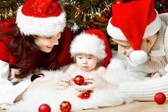 Julfamilj i röda hattar som ger gåvor Royaltyfri Bild