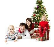 Julfamilj och grantree med gåvaaskar Arkivbild