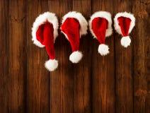 Julfamilj Santa Claus Hats Hanging på den Wood väggen, Xmas-hatt royaltyfri bild