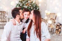 Julfamilj som ler och kysser nära Xmas-trädet Vardagsrum som dekoreras av julgran- och gåvagåvaasken royaltyfria foton