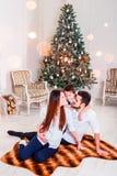 Julfamilj som ler och kysser nära Xmas-trädet Vardagsrum som dekoreras av julgran- och gåvagåvaasken arkivfoton