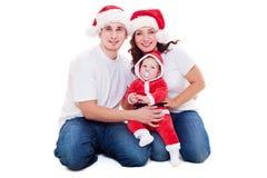Julfamilj som sitter på golv Arkivfoto