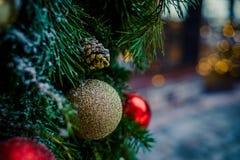 Julfamiljatmosfär Den röda guld- julprydnaden som hänger på en täckt frost, sörjer trädet utomhus med kopieringsutrymme royaltyfria foton
