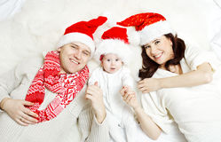 Julfamiljen med behandla som ett barn i röda hattar. Royaltyfri Fotografi