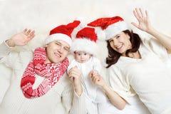 Julfamiljen med behandla som ett barn i röda hattar. royaltyfria bilder