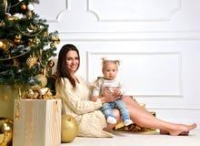 Julfamiljen med moderkvinnan med behandla som ett barn ungeflicka och guld c Royaltyfria Foton