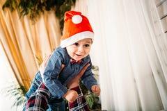 Julfamiljstående av den lyckliga le pysen i den röda santa hatten i händer för fader` s Begrepp för Xmas för vinterferie och för  royaltyfri foto