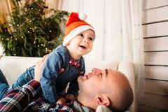 Julfamiljstående av den lyckliga le pysen i den röda santa hatten i händer för fader` s Begrepp för Xmas för vinterferie och för  arkivbilder