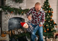 Julfamiljstående av den lyckliga le pysen i den röda santa hatten i händer för fader` s Begrepp för Xmas för vinterferie och för  royaltyfria bilder