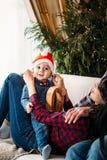 Julfamiljstående av den lyckliga le pysen i den röda santa hatten i händer för moder` s Xmas för vinterferie och nytt år arkivfoto