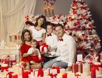 Julfamiljstående som firar Xmas-ferie, närvarande gåvor arkivbild