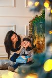 Julfamiljståenden av lyckligt le modersammanträde på golvet nära till spisen dekorerade med gran och girlanden och att ge sig royaltyfria bilder