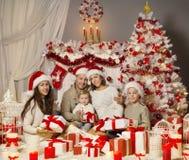 Julfamiljståenden, ferieXmas-träd, framlägger gåvor royaltyfri foto