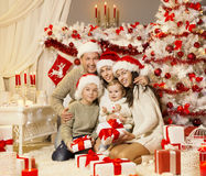 Julfamiljståenden, Xmas-träd framlägger gåvor, ferieberöm royaltyfri fotografi