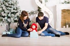 Julfamiljståenden i hem- ferievardagsrum, den närvarande gåvaasken, huset som dekorerar vid Xmas-trädet, undersöker girlanden Royaltyfria Bilder