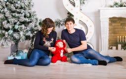 Julfamiljståenden i hem- ferievardagsrum, den närvarande gåvaasken, huset som dekorerar vid Xmas-trädet, undersöker girlanden Arkivfoto