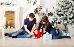 Julfamiljståenden i hem- ferievardagsrum, den närvarande gåvaasken, huset som dekorerar vid Xmas-trädet, undersöker girlanden Arkivfoton