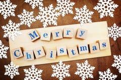 Julferiebakgrund med en hälsa text på träkuber och snöflingor royaltyfri bild