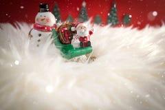 Julferiebakgrund med jultomten och garneringar Jul landskap med gåvor och snöar Glad jul och lycklig ny ye Arkivbild