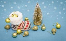 Julferiebegrepp Xmas-kängor med guldbollar och julgran på blå bakgrund med fallande snöflingor Royaltyfri Bild