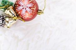 Julfestivalgarnering med den röda prydnadbollen på den fluffiga vita filten Arkivbilder