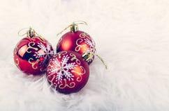 Julfestivalgarnering med den röda prydnadbollen på den fluffiga vita filten Royaltyfria Bilder