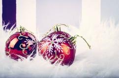 Julfestivalgarnering med den röda prydnadbollen på den fluffiga vita filten Royaltyfria Foton