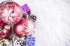 Julfestivalgarnering med den röda prydnadbollen på den fluffiga vita filten Arkivbild