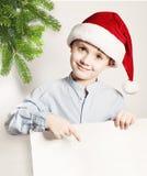 Julfilial och klockor Barnpojke i Santa Hat Showing White Banner Royaltyfria Foton
