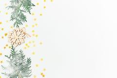 Julfilial och klockor Granfilialer och trägarnering med guld- konfettier på vit bakgrund Lekmanna- lägenhet, bästa sikt Royaltyfria Bilder
