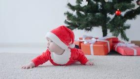 Julfilial och klockor Gulligt behandla som ett barn i dräkten av Santa Claus som ser en gåva lager videofilmer