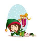 Julflickaälvan vilar med en stor gåva Royaltyfri Bild