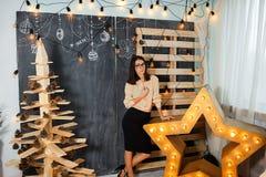 Julflicka i inre med stearinljus och ljus Arkivfoto