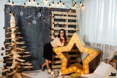 Julflicka i inre med stearinljus och ljus Arkivbilder