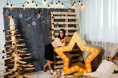 Julflicka i inre med stearinljus och ljus Arkivbild