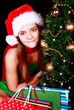 Julflicka med aktuella påsar över dark royaltyfria foton
