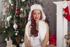 julflicka santa Härlig le kvinnamodell med långt lockigt Arkivfoto