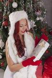 julflicka santa Härlig le kvinnamodell med långt lockigt Royaltyfria Bilder