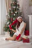 julflicka santa Härlig le kvinnamodell med långt lockigt Royaltyfri Foto