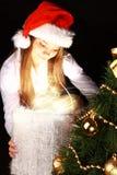 Julflicka som rymmer aktuell over dark arkivbild