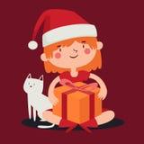 Julflicka som rymmer en gåva bredvid hennes älsklings- katt Royaltyfri Foto