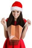 Julflicka som ser i shoppingpåse Royaltyfria Foton