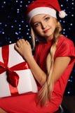 Julfoto av den gulliga lilla blonda flickan i den santa hatten och den röda klänningen som rymmer en gåva - ask Arkivfoto