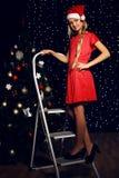 Julfoto av den gulliga lilla blonda flickan i den santa hatten och röd klänning Royaltyfri Fotografi