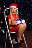 Julfoto av den gulliga lilla blonda flickan i den santa hatten och röd klänning Fotografering för Bildbyråer