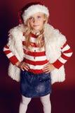 Julfoto av den gulliga lilla flickan med långt blont hår i jultomten hatt, pälslag som ler och poserar i studion Arkivbild