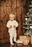 Julfoto av den lilla gulliga pojken som spelar med leksaker, i dekorerat royaltyfria bilder