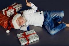 Julfoto av pysen i den santa hatten och jeans som ler med julgåvor, gåva Arkivbilder