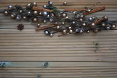 Julfotografi med silver och den guld- kulöra ekollonträdprydnaden på naturlig lantlig wood bakgrund med kryddan för stjärnaanis arkivbilder
