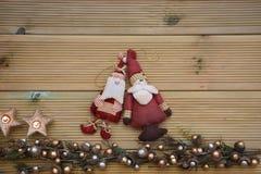 Julfotografi med silver och den guld- kulöra ekollonträdprydnaden på naturlig lantlig wood bakgrund med santa garneringar royaltyfri bild